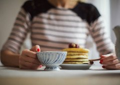Woman eating pancakes and drinking tea.