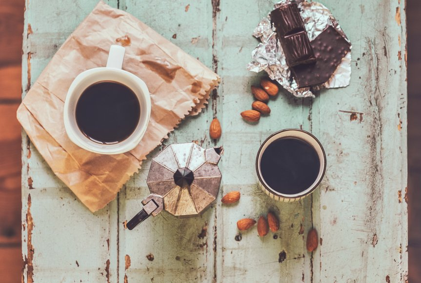 Vintage table wtih two cups of coffee, a macchinetta, dark chocolate, and almonds.
