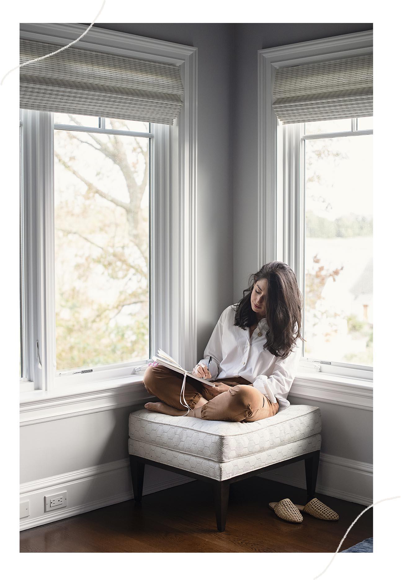 Jamie Mendell, Life Alchemist, sitting on an ottoman chair writing