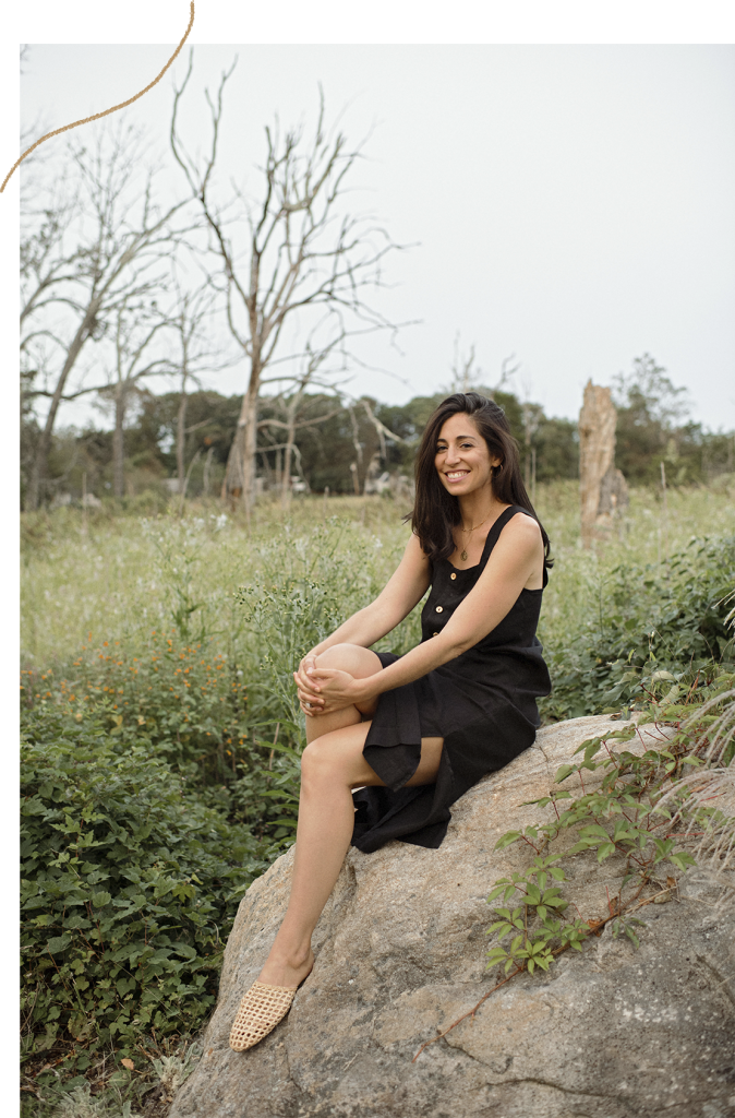Jamie Mendell, Life Alchemist, sitting on a rock in a field